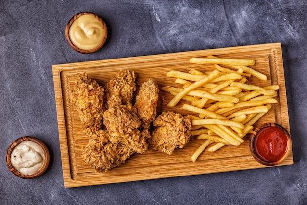 Fried chicken wings with french fries, top view.