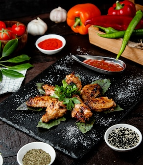 Fried chicken wings with sauce in black dishes