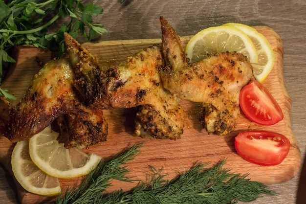 Fried chicken wings with tomato and lemon on a wooden board with parsley and dill