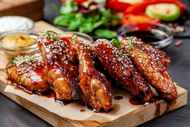 Fried chicken wings with tomato sauce and sesame seeds