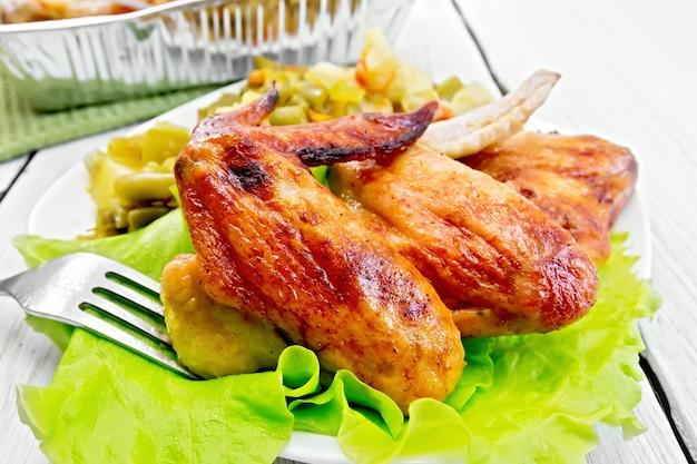 Жареные куриные крылышки с овощами и листьями салата на тарелке, вилкой на фоне легких деревянных досок
