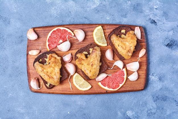 Ali di pollo fritte su una tavola di legno sull'azzurro