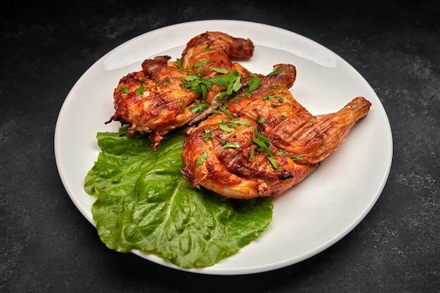Жареный цыпленок с аппетитной хрустящей корочкой, с листьями салата, на белой тарелке, на черном фоне