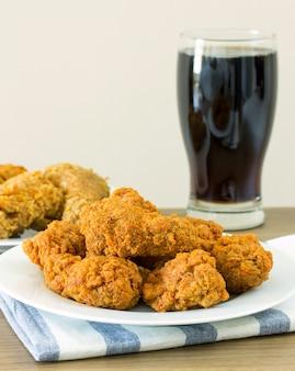 Жареный цыпленок с колой на обеденном столе
