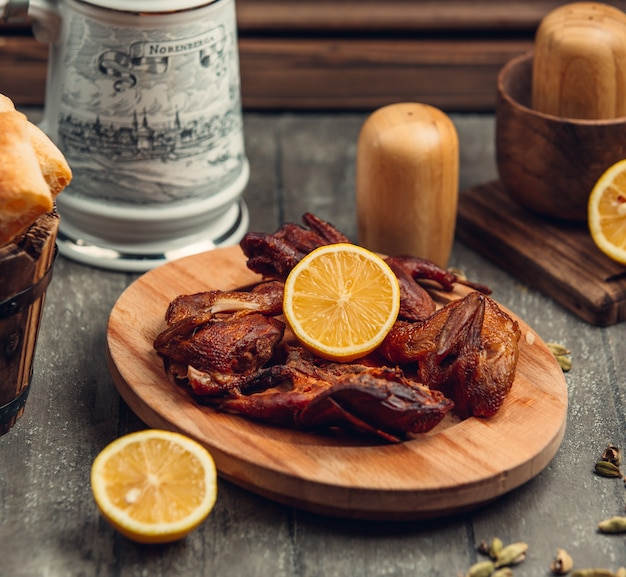 Fried chicken with lemon on the wooden board