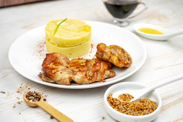 Жареный цыпленок в горчично-медовом соусе с картофельным пюре на белой тарелке