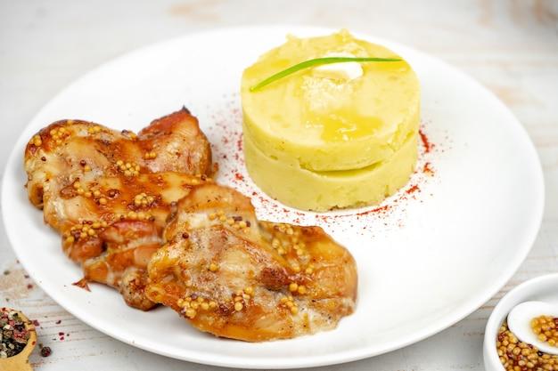 Жареный цыпленок с горчично-медовым соусом с картофельным пюре на белой тарелке