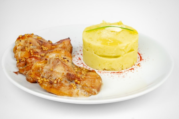 Fried chicken with mustard and honey sauce with mashed potato on white background