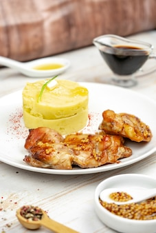 Fried chicken with mustard and honey sauce with mashed potato on white plate
