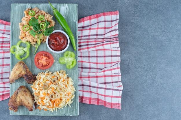 Жареный цыпленок с рисом и макаронами на деревянной доске.