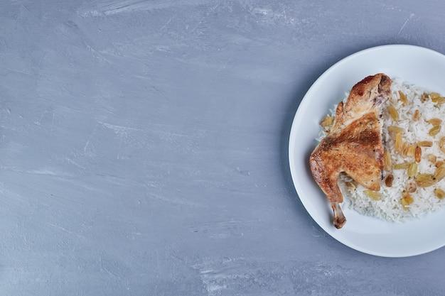 흰 접시에 쌀 장식과 함께 프라이드 치킨.