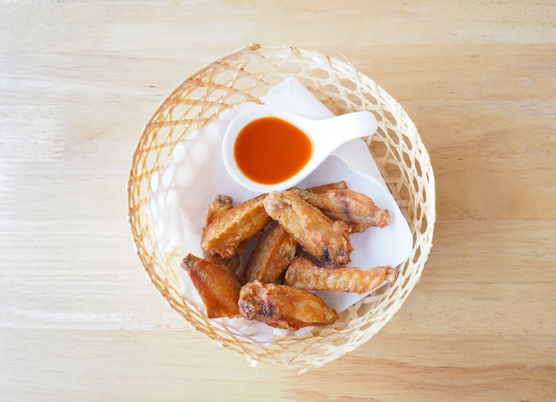 Fried chicken with sauce in bamboo basket on wooden table