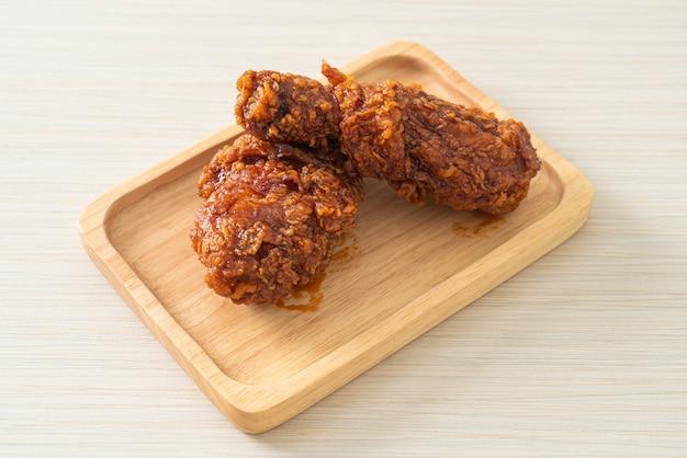 나무 접시에 매운 한국 소스를 곁들인 프라이드 치킨