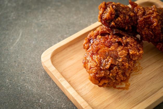 Жареный цыпленок с острым корейским соусом на деревянной тарелке