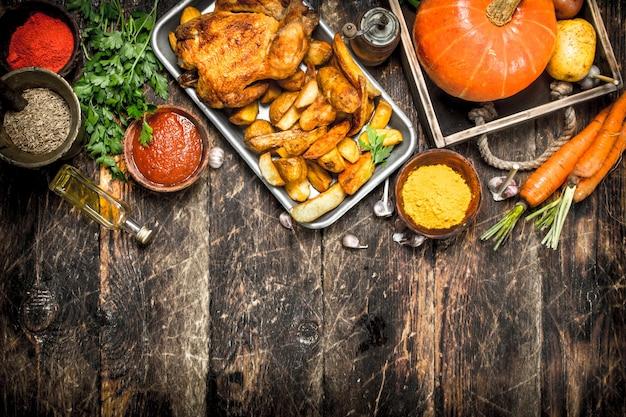 木製のテーブルに野菜とスパイスを添えたフライドチキン。
