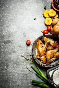Жареный цыпленок с овощами и томатным соусом на каменном фоне