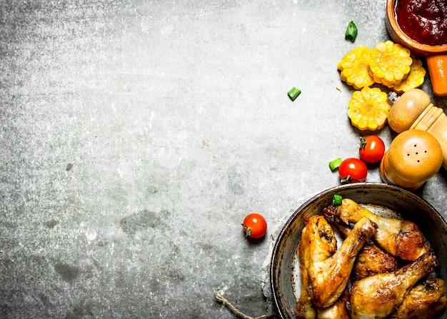 Жареный цыпленок с овощами и томатным соусом. на каменном фоне.