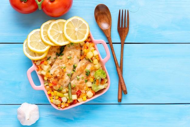 フォークとスプーンで木製の背景のプレートに野菜とフライドチキン。