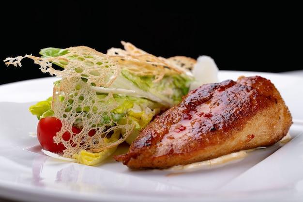 白い皿の上の野菜とフライドチキン。白色の背景。