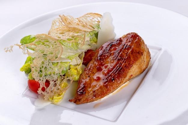 白い皿の上の野菜とフライドチキン。白い表面。
