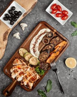 Pollo fritto con verdure su una tavola di legno