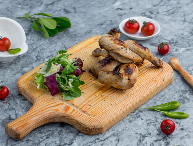 Fried chicken with vegetables on wooden board