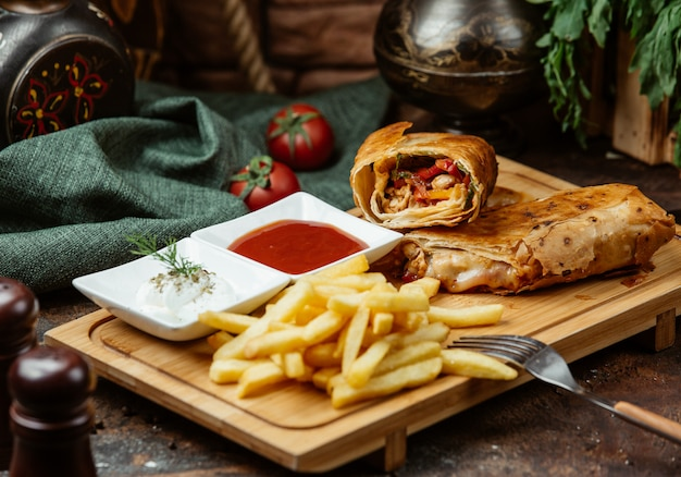 Fried chicken wrap with tomato, bell peppers, french fries, sauces