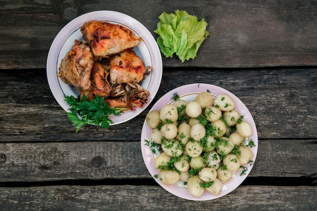 Fried chicken and young potatoes with dill.simple rural dish.wooden wall.top view