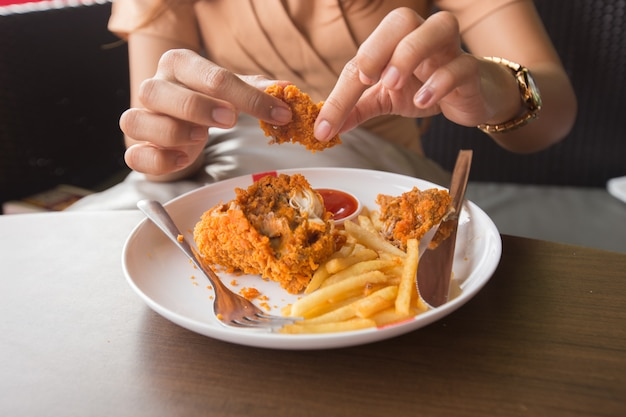 Fried chicken in young woman hand select focus
