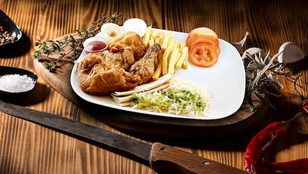 フライドポテトと木のテーブルのソース炒め鶏