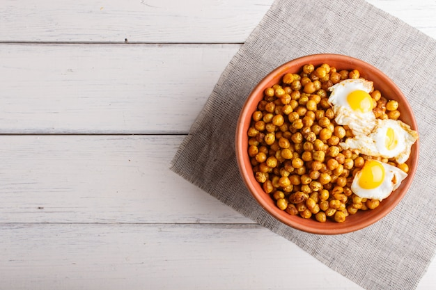 Fried chickpeas with quail eggs and spices in a clay plate