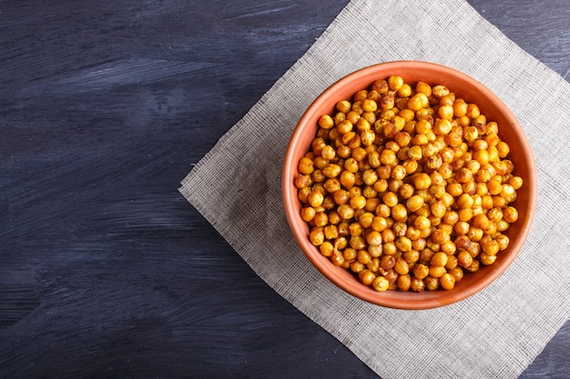 Fried chickpeas with spices in a clay plate on black wooden surface.