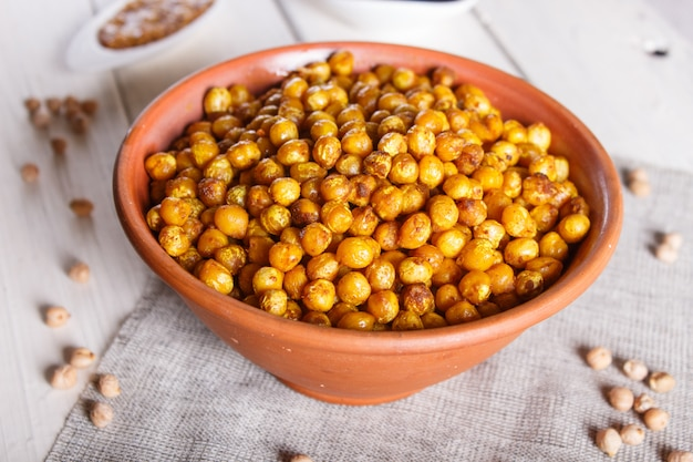 Fried chickpeas with spices in a clay plate on white wooden surface.
