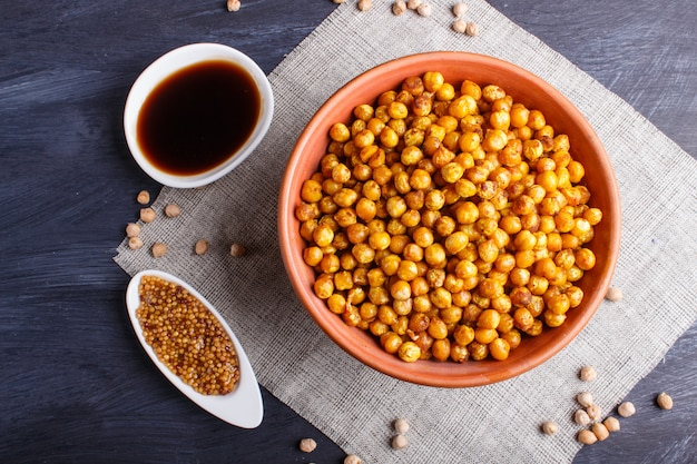 Fried chickpeas with spices in a clay plate