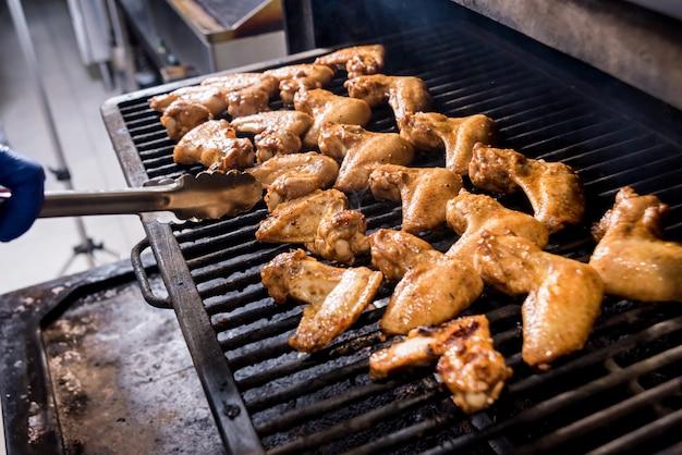 Жареные куриные крылышки на гриле для барбекю. ресторан. Premium Фотографии