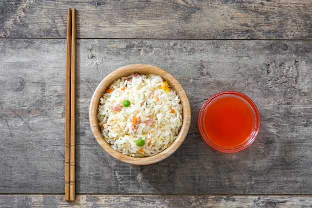 Fried chinese rice with vegetables on wooden table top view