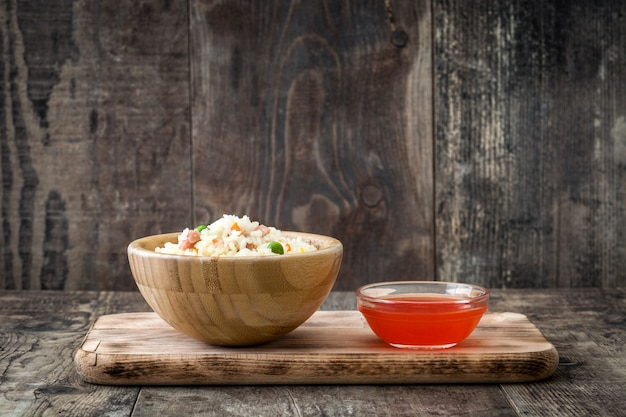 Fried chinese rice with vegetables on wooden table