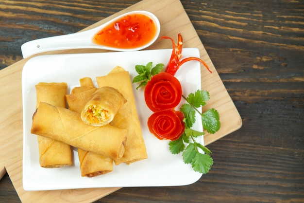 Fried chinese spring rolls served with chili sauce and decorated rose tomatoes with green leaved on wood, space. concept asian food