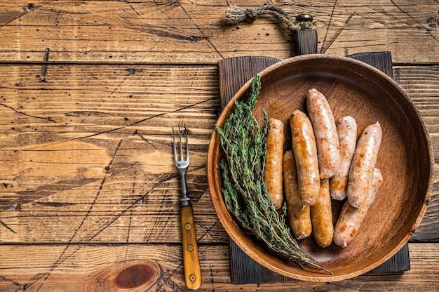 Жареные сосиски чоризо и братвурст в деревянной тарелке. деревянный стол. вид сверху.