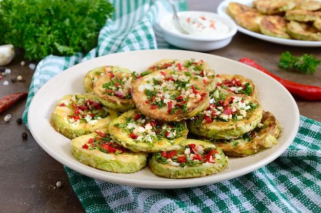 Жареные кружочки молодого цуккини с чесноком, красным перцем, зеленью на тарелке. вегетарианское меню. закрыть