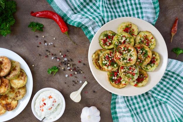 Жареные кружочки молодого цуккини с чесноком, красным перцем, зеленью на тарелке. вегетарианское меню. вид сверху.