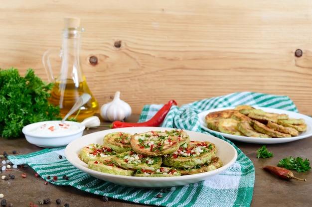 Жареные кружочки молодого цуккини с чесноком, красным перцем, зеленью на тарелке. вегетарианское меню.