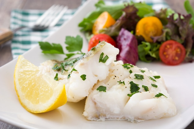 Fried cod fillet and salad on wooden table  close up
