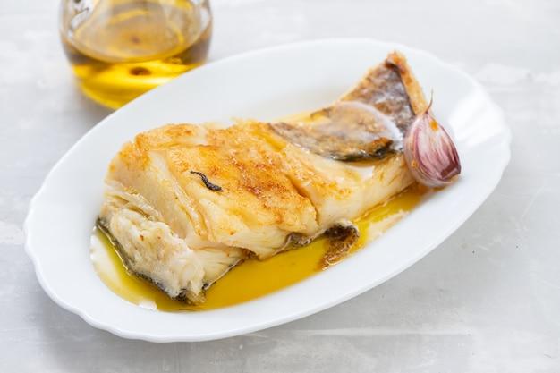 白い皿にニンニクとオリーブオイルで揚げたタラの魚