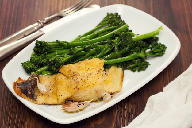 Fried cod fish with greens on white plate