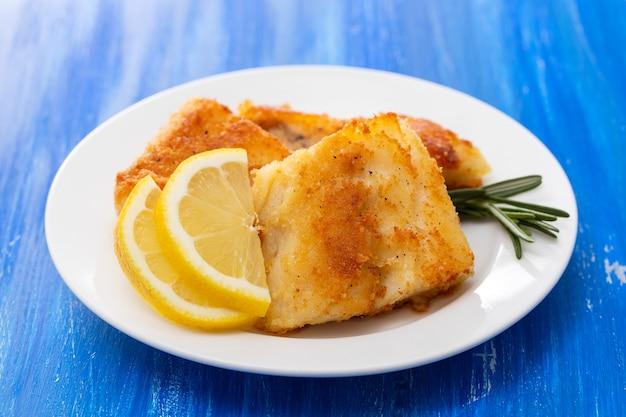 Жареная треска с лимоном на белой тарелке