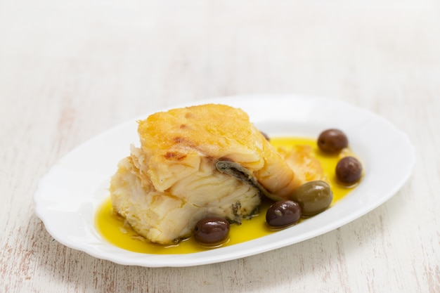 Fried cod fish with olives and olive oil on white dish