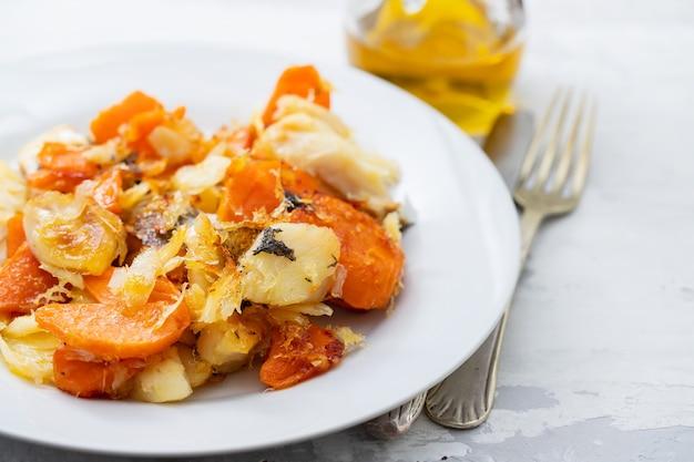Fried cod fish with sweet potato on white dish on ceramic background