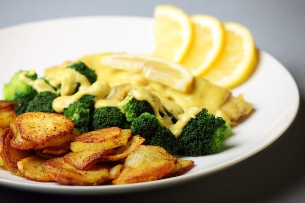 Жареная треска с нарезанным картофелем, брокколи и соусом бешамель