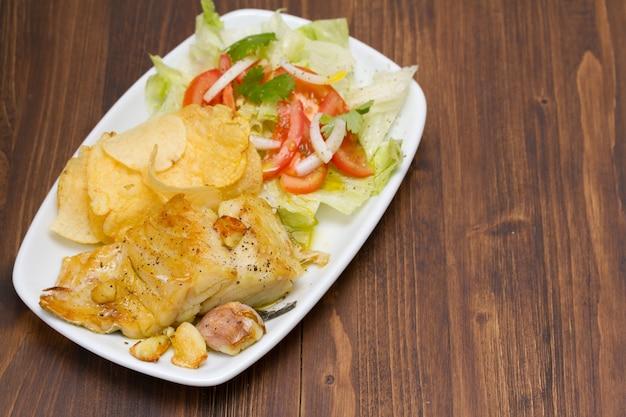 Жареная треска с картофелем и салатом на блюде